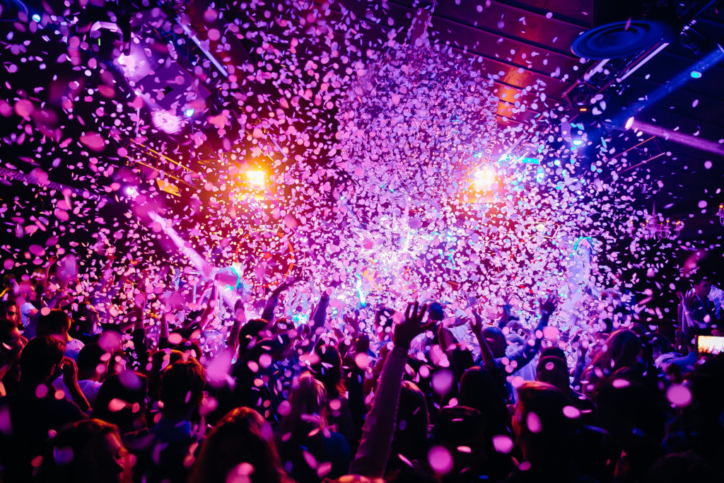 Praxis Insurance Associates - Hospitality Insurance - Concert crowd - picture with a lof of people dancing i a concert, night club with raised their hands up! Amazing colours!